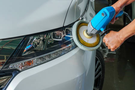 Big headlight cleaning with power buffer machine at service station