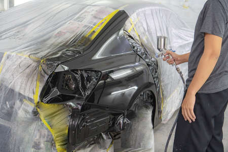 Man with protective clothes and mask painting car using spray compressor