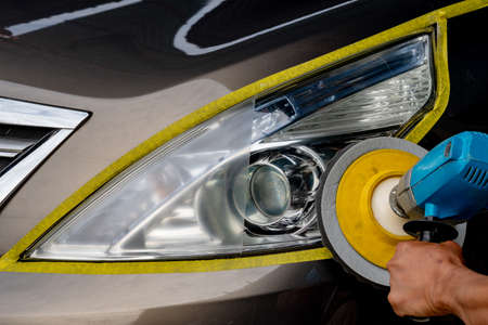 Big headlight cleaning with power buffer machine at service station ,Before and after cleaning Banco de Imagens