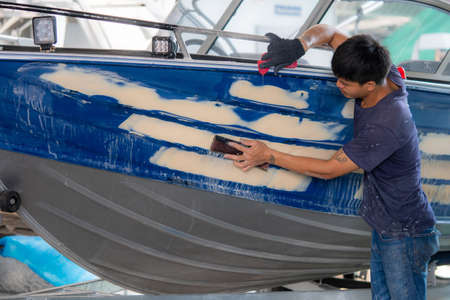 Repairing boat body by puttying close up work after the accident by working sanding primer before painting 免版税图像