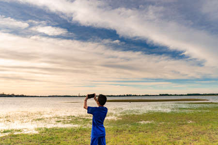 A boy takes pictures at sunset with the phone