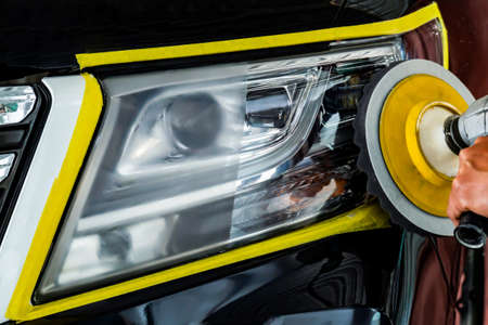 Big headlight cleaning with power buffer machine at service station ,Before and after cleaning Imagens