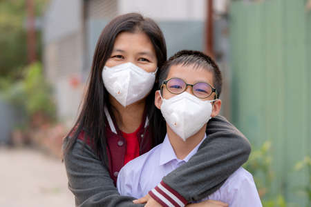 Mather and son with dust protection mask ( Safety Mask )on the street 스톡 콘텐츠
