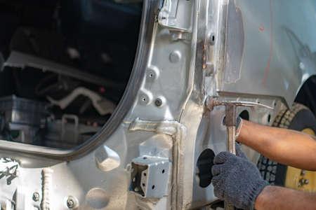Reparatur von Autobeulen mit Hammer und Klopfen, Machen Sie die Oberfläche des Autos glatt und bereiten Sie es auf die Lackierung am Bahnhof vor. Arbeiter repariert Autokarosserie Standard-Bild