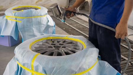 Automobile disc restoring. Painter painting light alloy wheel with spray Stock fotó