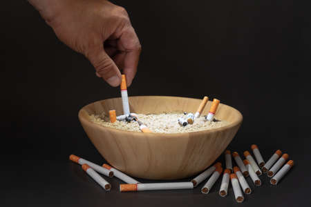 Many cigarettes are placed in a wooden cup of sand on a black background. ,The male hand is extinguishing the cigarette