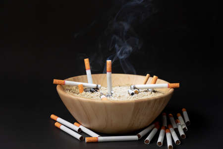 Many cigarettes are placed in a wooden cup of sand on a black background. Imagens