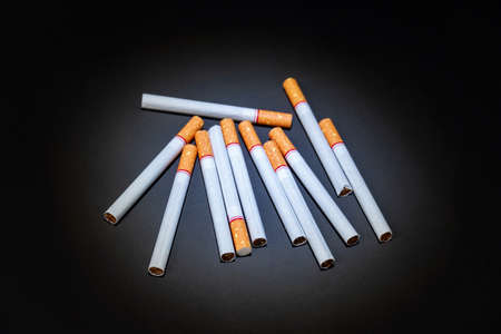Many cigarettes are placed on a black background.