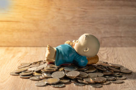 Clay doll on Thai coin pile ,wood background