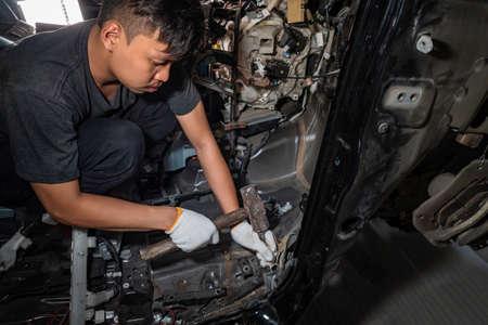 Le réparateur de la carrosserie utilise un marteau pour casser le fer endommagé. ,Série de réparation de carrosserie: Fixation de carrosserie