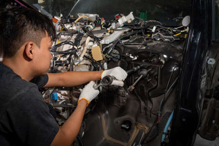 The car mechanic is checking the car after the accident, car electrician repairs car Imagens