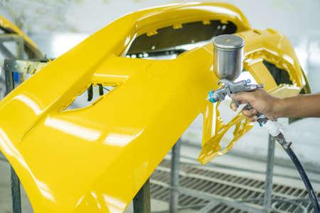 Homme avec des vêtements de protection et une voiture de peinture de masque à l'aide d'un compresseur de pulvérisation, pare-chocs avant jaune