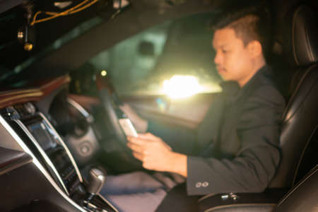 Men are playing mobile while driving. , May cause accidents , ,Blur background