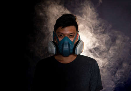 man in a gas mask smokes and breathes a cloud of tobacco smoke ,black background Imagens