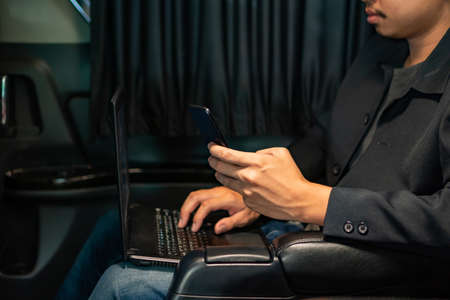 Smart young businessman using laptop and mobile in luxury automobile, working , Imagens