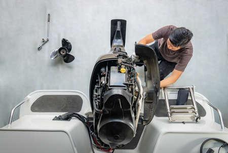 Reparatur von Motoren auf Aluminiumbooten, Der Techniker entfernt die Bootsteile, um den Lack herzustellen