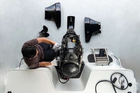 Repairing engines on aluminum boats , The technician is removing the boat parts to make the paint Imagens