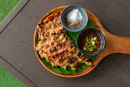 Grilled beef steak with spicy sauce on a wooden plate Stock Photo