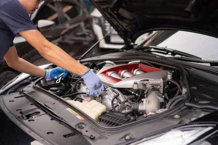 Professional mechanic checking car engine ,Auto mechanic working in garage. Repair service. 版權商用圖片