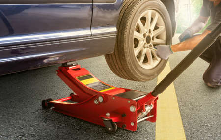Red hydraulic  floor jack ,Asia man with a blue car that broke down on the road.Changing tire on broken car on road
