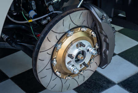 Automobile braking system. Ceramic carbon disk with perforation, ventilation and black calipers.