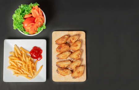 fast food , french fries and fried chicken , with green salad, tomatoes on dark table, top view Imagens