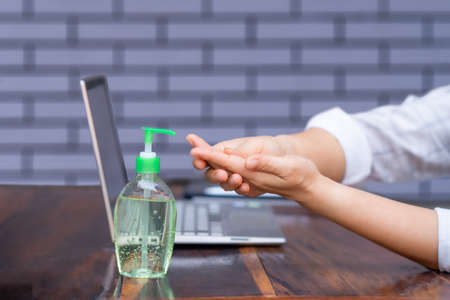 Asian girl , Cleaning hands by liquid alcohol, to prevent germs on a white background ,Washing hand with Alcohol Sanitizer ,covid-19