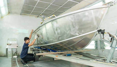 The mechanic is using a metal grinder. , Surface preparation, boat body, for spray painting ship