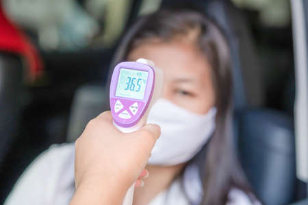 Female Doctor Checking Temperature Using Infrared Thermometer,Tool for detect coronavirus or covid-19 ,The lady in the car