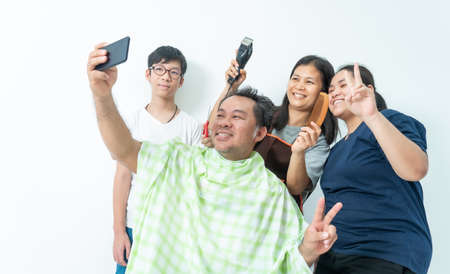 Husband, wife and daughter, son taking a selfie While cutting his hair