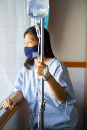 A sick Asian woman wear mask, in a  hospital with IV saline drip to back of the hand. Corona Virus or Covid-19 concept. Imagens