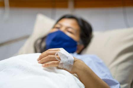 A sick Asian woman wear mask and lying on bed in hospital with IV saline drip to back of the hand. Corona Virus or Covid-19 concept.