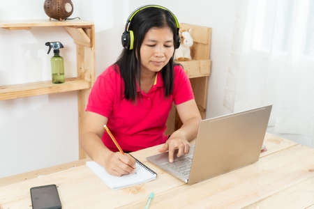 A happy, casual woman working on a laptop sitting at a desk in the house Imagens