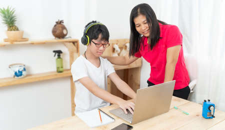 Mother is teaching her son, studying online at home. Online lesson for children. Child studying from home with the help of the mother. Work from home.