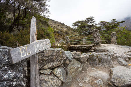path with a pedestrian bridge to El Montos in Venezuelan Andes, indication with the text
