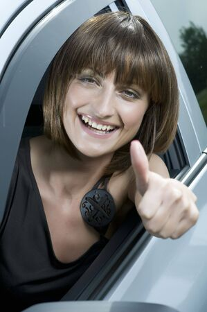Happy beautiful young woman smiling in a car with thumbs up. Stock Photo - 7200497