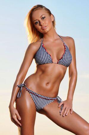 Young beautiful tanned woman in bikini on beach.