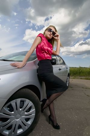 Blond girl in sunglasses is near a car on the road.  photo