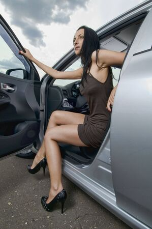Sexy young woman sitting in her car photo