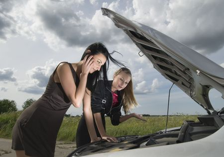 Two young women with broken down car Stock Photo - 7260829