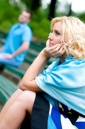 acquaintance: Young woman and man sitting on a bench in park, selective focus
