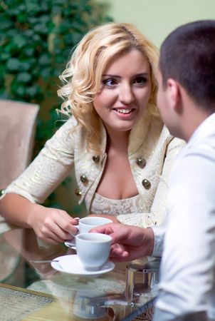 Happy smiling couple in cafe with cups in hands photo