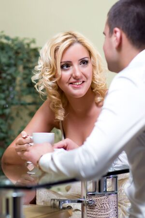 Young happy couple drinking coffee in a restaurant photo