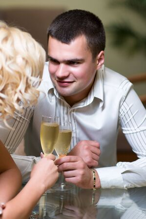 Young couple sharing champagne glasses in a restaurant,  on romantic date. Focus on male  photo