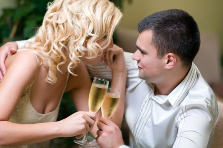 Young couple celebrating with champagne together, in restaurant photo