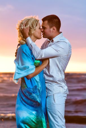 Beautiful young couple in love near the sea at sunset photo