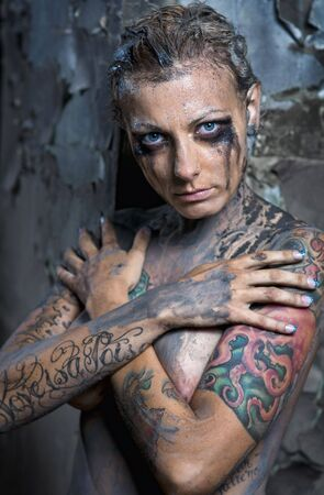 Tattooed young naked woman with smeared make-up Stock Photo - 7413067