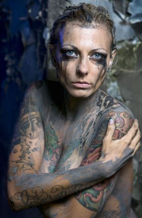 Naked tattooed woman with smeared makeup photo