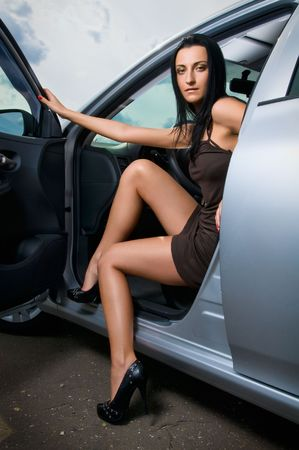 Young beautiful brunette sitting in a car photo