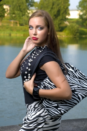 green lipstick: Brown haired pretty woman with handbag outdoors  Stock Photo